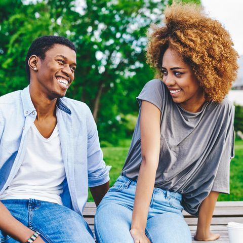 Ein Mann und eine Frau flirten auf einer Parkbank