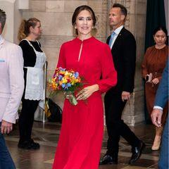 """Bei diesem Look stimmt einfach alles! Prinzessin Mary zeigt sich bei der offiziellen Eröffnung von """"Copenhagen 2021"""" in Verbindung mit WorldPride und EuroGames im Rathaus in Kopenhagen in einem Outfit, das jedem noch so trostlosen Regentag ein sommerliches Flair verleiht. Zum knallig roten Mididress kombiniert sie spitze Wildleder-Heels im gleichen Farbton. Der Blumenstrauß, den die Prinzessin vermutlich geschenkt bekommen hat,fügt sich perfekt in das Gesamtbild ein."""