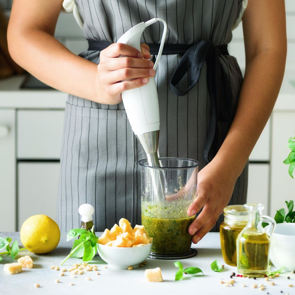 Stabmixer-Test: Diese Modelle können überzeugen, Frau bereitet grünes Pesto zu