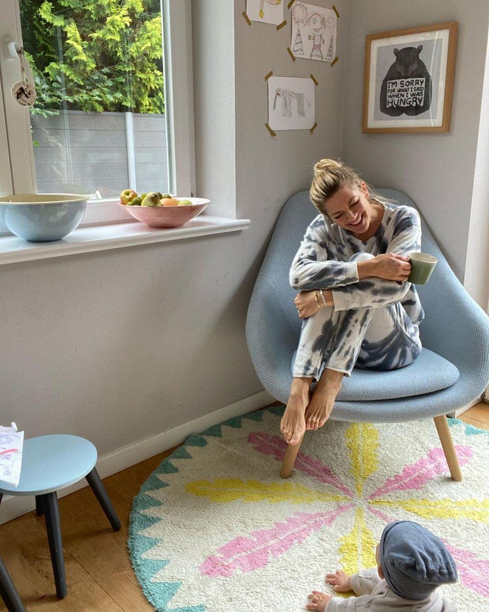 """Ihre """"Good Morning Vibes"""" teilt Nina Bott mit ihren Fans auf Instagram. Ein Foto zeigt sie in einem Traum aus Pastell in ihrem Hamburger Haus. Das Zimmer ist freundlich und im angesagten Scandi-Style eingerichtet. Babyblaue Möbel reihen sich an zartes Rosa und sonnigesGelb. Die bunten Farben sorgen in Kombination mit Holzelementen für einen urbanen Look. Besonders süß: An der Wand hängen gemalte Bilder der Kids, die die Schauspielerin mit bunten Klebestreifen angebracht hat – ein praktischer Mama-Trick.Während Nina Bott ihr erstes Heißgetränk des Tages genießt, strahlt sie Söhnchen Lobo an. Der Kleine krabbelt munter auf dem flauschigen Teppich herum."""