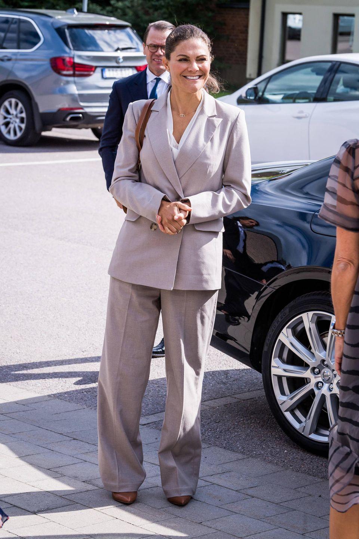Zum grauen Zweiteiler, bestehend aus weiter Bundfaltenhose und Zweireiher, kombiniert Victoria ein schlichtes weißes Shirt mit V-Ausschnitt und spitze Heels in braun. Zwar ist der Look dem Anlass durchaus angemessen, wirklich vorteilhaft ist er für die Thronfolgerin allerdings nicht.