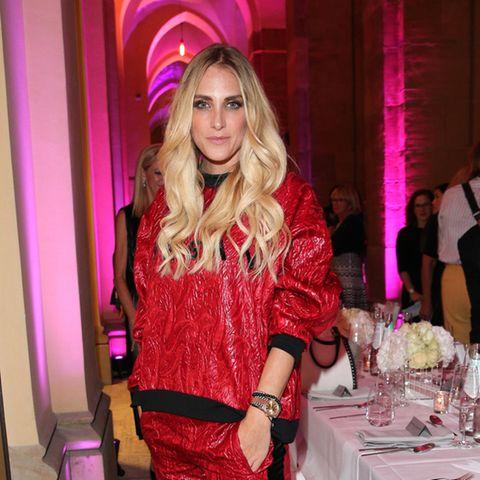 Anna Kraft in einem roten Outfit vor einer festlichen Tafel