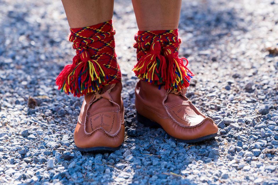 Besonderer Hingucker: die nach vorne hin spitz zulaufenden Schuhe aus cognacfarbenem Leder samt bunter Lederbänder am Schaft