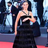 """Sara Sampaio hat allen Grund zum Strahlen. Die Robe aus dem Hause Armani Privé mit Streifen aus Samt und extravaganten Trägern steht dem """"Victoria's Secret""""-Model einfach hervorragend!"""