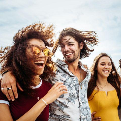 Vier junge Leute liegen sich lachend in den Armen und versprühen positive Energie.