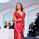 Blutrot glänzt Zoe Saldanas Red-Carpet-Look von Dolce & Gabbana im abendlichen Sonnenlicht von Venedig.