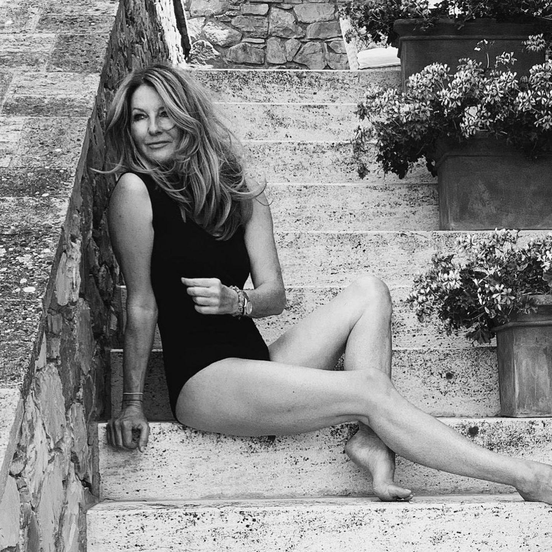 Frauke Ludowig posiert auf den Stufen einer Treppe im Badeanzug für ein Foto.