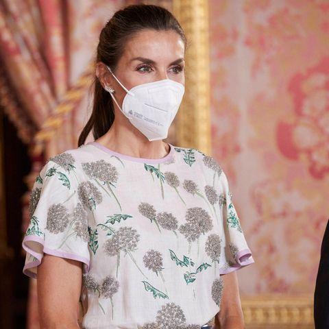 Erst bei genauerer Betrachtung fallen die aufwendig gestalteten Blumenmotive von Königin Letizias Kleid auf. Zahlreiche Glitzersteine sind in dem Top des Kleides verarbeitet. Passend dazu kombiniert Letizia kleine Feder-Ohrringe von Chanel, eine ganz andere Schmuckwahl als ihre Schwiegermutter damals.