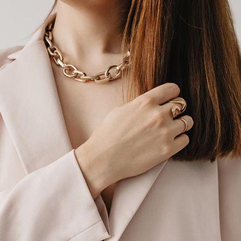 Eine Frau trägt eine goldene Statementkette sowie Ringe.