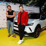 Team Opel Mokka: Modedesigner Marcel Ostertag posiert lässig mit Sänger und Opel-Mokka-Botschafter Nico Santos vor dem neuenOpel Mokka-E, der bei der Show präsentiert wurde.