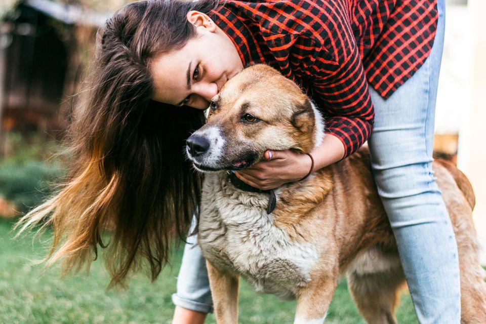 Persönlichkeitstest: Frau kuschelt mit Hund