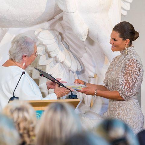 Prinzessin Christina übergibt Kronsprinzessin Victoria die Auszeichnung auf einer Bühne.