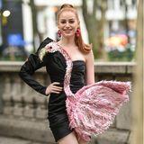 ''Riverdale''-Star Madeleine Petsch zeigt sich vor der Moschino-Show in einem extravaganten Kleid des gleichnamigen Designers. Die Besonderheit des Looks: Dasschwarze Minidress wird durch einen rosa Glitzer-Flamingo verziert.