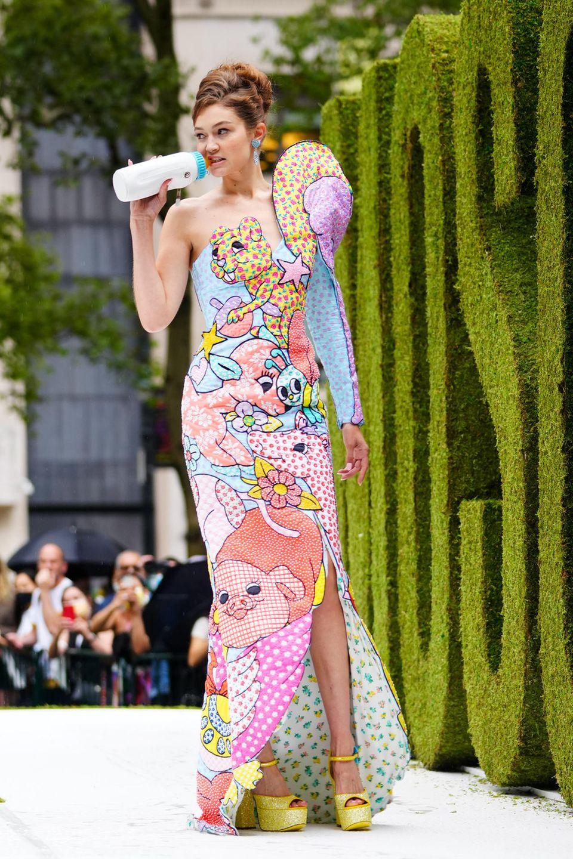 Moschino feiert in diesem Jahr sein Debüt auf der New York Fashion Week. Zu diesem besonderen Anlass trägt Model Gigi Hadid auf dem Laufsteg der Show ein langes One-Shoulder-Dress mit ausgefallener Schulterpartie. Der Hingucker des Outfits: In der rechten Hand hält die schöne Blondine eine Babyflasche, an der sie mit lässigem Blick Richtung Publikumnuckelt.