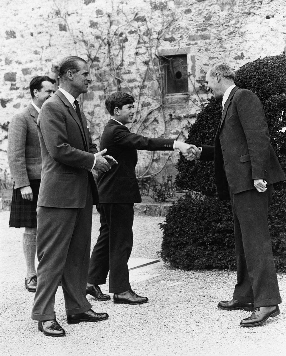 """Prinz Charles schüttelt Robert Chew, dem damaligen Schulleiter der """"Gordonstoun""""-Schule, am1. Mai 1962die Hand. Er wurde an seinem ersten Tag von seinem Vater Prinz Philip, der auch die Schule besucht hat, begleitet."""