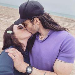 """Total verliebt zeigen sich """"2 Broke Girls""""-Star Kat Dennings und Musiker Andrew W.K knutschend am Strand. Die beiden hatten sich Ende April 2021 verlobt, und nun warten ihre Fans bei solch innigen Selfies natürlich ganz besonders gespannt darauf, wann es denn endlich soweit ist mit ihrer Heirat. Eine Spannung, die wir teilen!"""