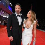 Es ist wohl DER Red-Carpet-Moment der diesjährigenFilmfestspielen in Venedig: Ben Affleck und Jennifer Lopez treten als Paarvor die Presse. Aber nicht in irgendeinem Outfit, nein. Es ist ein weißes Haute-Couture-Kleid von Georges Hobeika mit einem Steinchen-besetzten Dekolleté, das wenig Spielraum für Fantasie lässt. Ben setzt auf einen schwarzen Anzug mit Fliege. Gewollt oder nicht: Ihr Auftritt wecktAssoziationen; die eines Hochzeitspaares.