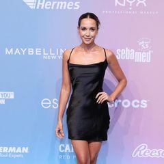 Mandy Capristo setzt bei den About You Fashion Awards in Berlin auf ein schlichtes Satin-Slip-Dress in Schwarz. Schwarze Sandaletten und ein tief sitzender Dutt perfektionieren ihren simplen, aber nicht weniger elgeanten Red-Carpet-Look.