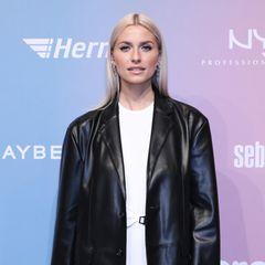 Auch Model und Unternehmerin Lena Gercke setzt auf Leder. Und zwar in Form eines Oversize-Blazers, den sie über einem weißen Kleid trägt.