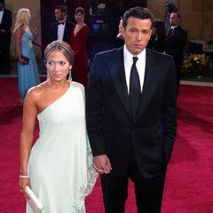 Beinahe schüchtern wirken Jennifer Lopez und Ben Affleck nachdem sie den Red-Carpet der Oscars im Jahr 2003 betreten haben. J.Lo trägt ein One-Shoulder-Dress mit Glitzer-Applikationen am Saum in der Farbe Weiß. Ben trägt einen schwarzen Anzug mit Krawatte. Unsichere Blicke, die Hände ineinander verankert.