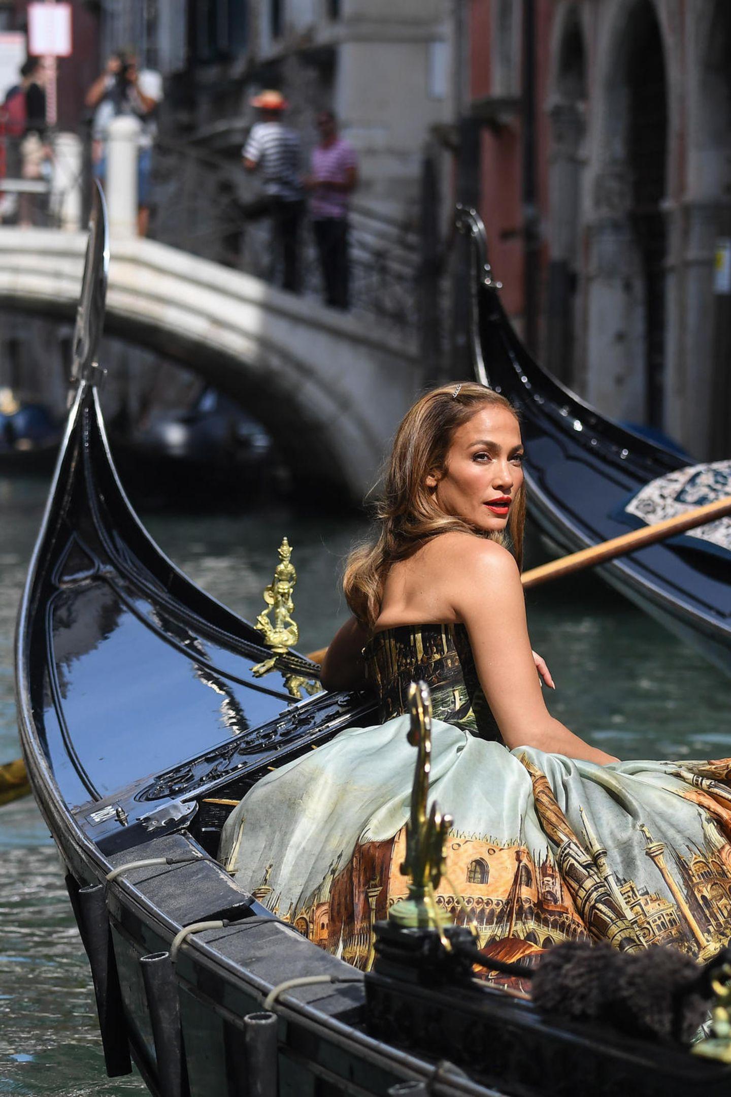 """Wenn wir dieses Bild von Jennifer Lopez in Venedig sehen, dann fällt es uns wirklich schwer zu glauben, dass sie """"immer noch Jenny aus dem Block"""" ist. Denn es hat schon etwas märchen- fast divenhaftes, wie J.Lo in ihrem Dolce-und-Gabbana-Kleid in der Gondel sitzt und über die Schulter in die Kamera blickt."""