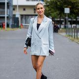 Mutig, mutiger, Alena Gerber! Die 32-Jährige funktioniert ihren Blazer kurzerhand um und trägt das hellblaue Kleidungsstück zugeknöpft als kurzes Kleid. Dazu kombiniert sie eine Chanel-Tasche und schwarze Boots von Bottega Venetta.