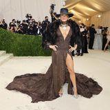 Howdy!Jennifer Lopez setzt auf ein Kleid mit Beinschlitz und XL-Ausschnitt von Ralph Lauren. Dazu kombiniert sie Hut, Felljacke und auffälligen Schmuck.