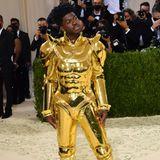 Rapper Lil Nas X erscheint in einer Art goldener Ritterrüstung. Ein spannender Look für solch ein Event.