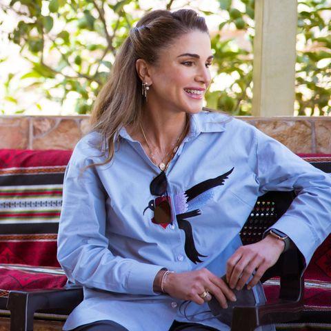 Königin Rania trägt eine blaue Bluse mit Stickereien