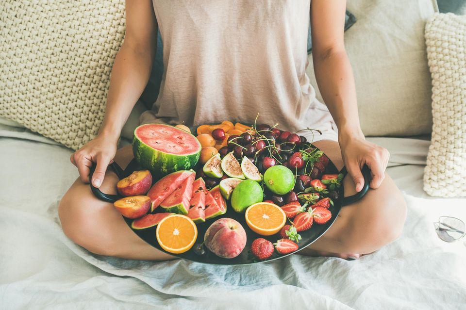 Frau hält einen Obstkorb mit Früchten wie Orangen, Wassermelone, Erdbeeren, Kirschen