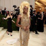 Drag Queen Symone will mit ihrem goldenen Dress von Moschino und tupierten Haaren hoch hinaus.