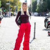 Model und Influencerin Trixie Giese begeistert mit diesem Streetstyle-Look: Zu einer extravaganten Hose in rotem Farbton kombiniert sie einen schwarz-roten Body.