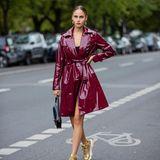 Model und Schauspielerin Elena Carriere trägt einen burgunderfarbenen Trenchcoat in Lack-Optik. Zu dem ausgefallenen Mantel wählt sie goldene Sneaker und macht mit der Kombination den Streetstyle-Look perfekt.