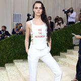 """Auch Cara Delevingne nutzt die berühmten Stufen vor dem Metropolitan Museum of Art für Ansagen und setzt in ihrem weißen Dior-Look mit dem Spruch """"Peg the Patriarchy"""" ein feministisches Statement."""