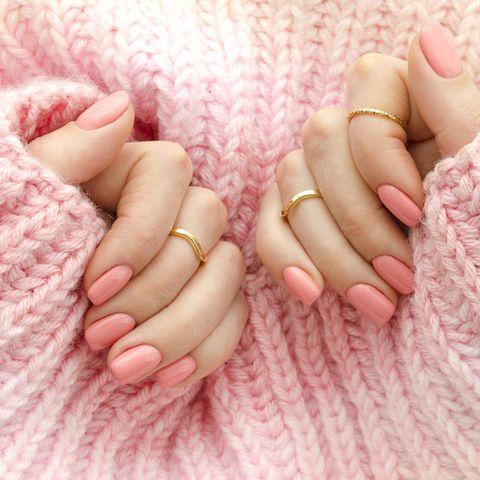 Nagelform: Hände mit rosafarbenen Fingernägeln auf einem rosafarbenem Wollpullover