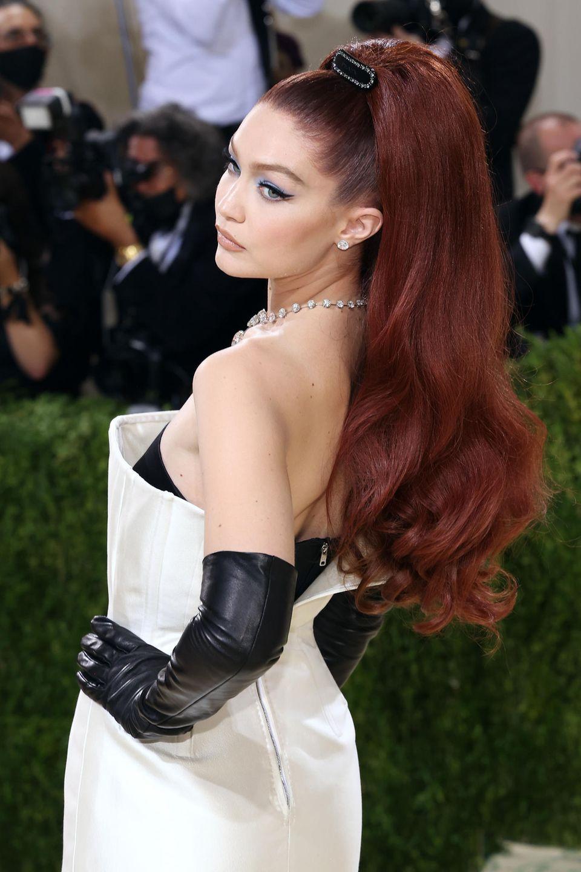 Gigi Hadid setzt auf einen Retro-Look mit feurig roten Haaren, hellblauem Lidschatten und einem dicken Lidstrich.
