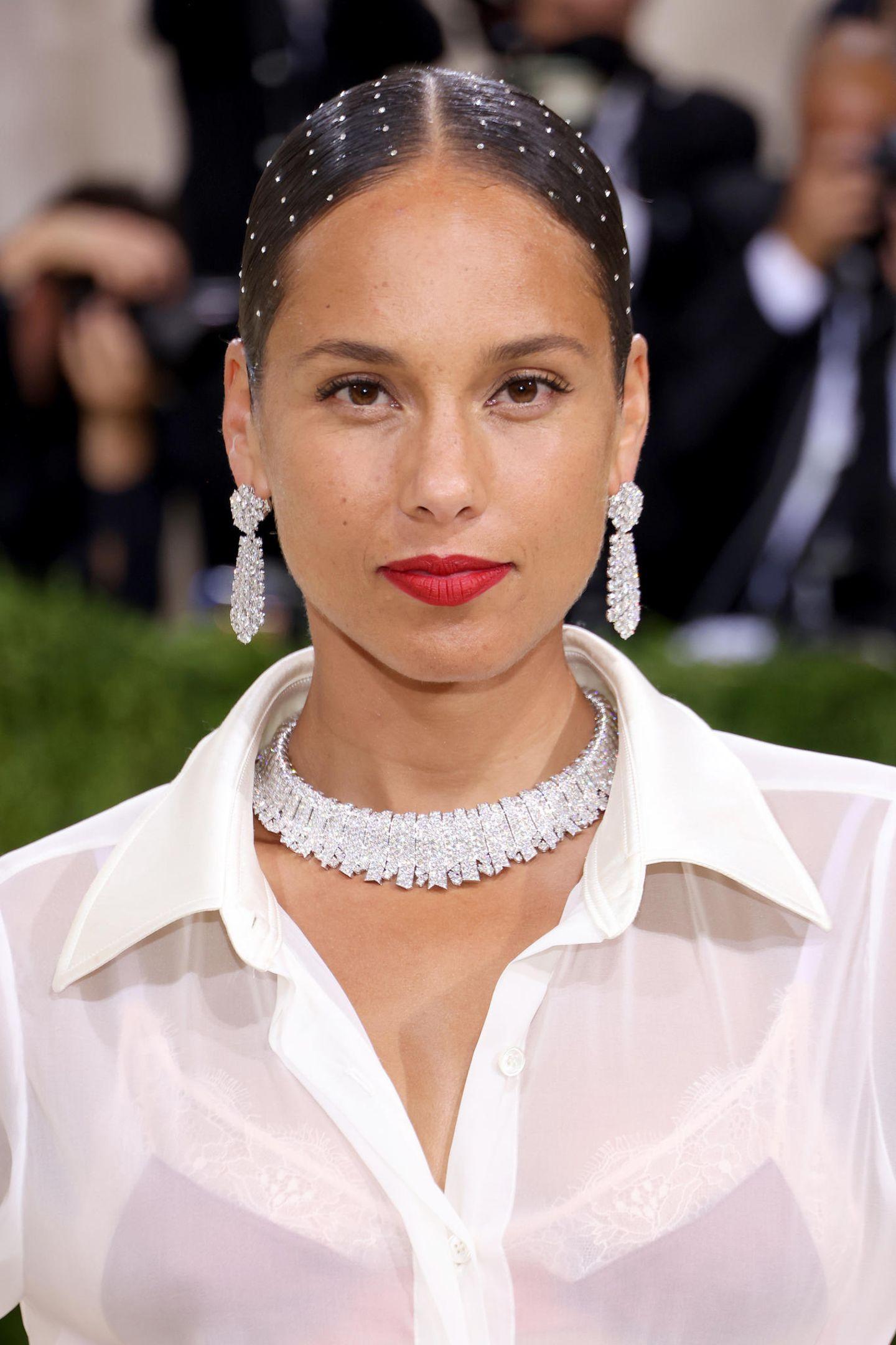 Alicia Keys wagt mit Glitzersteinchen auf ihren Haaren etwas Neues. An der Make-up-Front setzt die Sängerin auf edle rote Lippen.