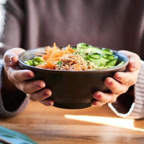 Das verraten Ihre Essgewohnheiten über Sie: Frau hält Poké-Bowl in der Hand.