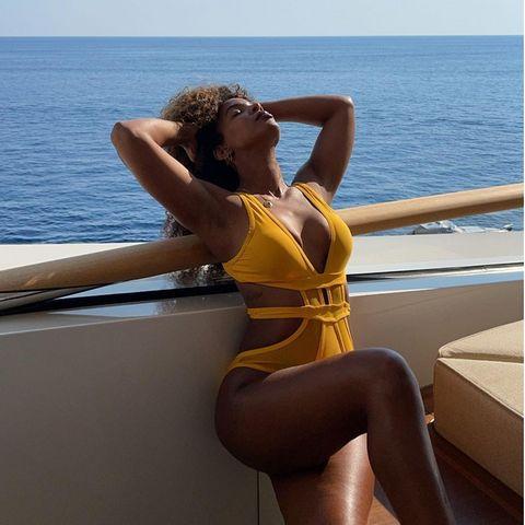 Kelly Rowland trägt einen gelben Badeanzug
