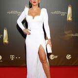 Evelyn Burdecki sorgt bei auf dem roten Teppich des deutschen Fernsehpreises 2021 für einen glamourösen Moment. Sie trägt ein weißes Kleid mit hohem Beinausschnitt und tiefemDekolleté, dazu ihr Markenzeichen: rote Lippen.