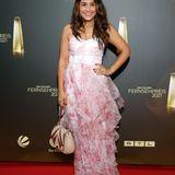 Nina Moghaddam kommt in einem sommerlichen Look zum deutschen Fernsehpreis – in einem rosafarbenen Corsagenkleid mit Chiffonvolants und akzentuierter Taille.