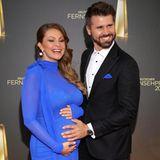 Einer der schönsten Auftritte auf dem roten Teppich:Jana Schölermann und Ehemann Thore. Sie trägt ein royalblaues, hochgeschlossenesKleid. Das süßeste Accessoire hält sie liebevoll in den Händen: ihren Babybauch.