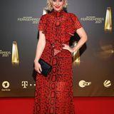 Passend zum roten Teppich schreitet Ruth Moschner in einer knallig roten Robe mit elegantem Python-Print über den roten Teppich beim deutschen Fernsehpreis 2021.