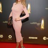 Jenny Elvers trägt ein hautenges Strickkleid in zartem Rosé, dazu Accessoires mit Leo-Muster.