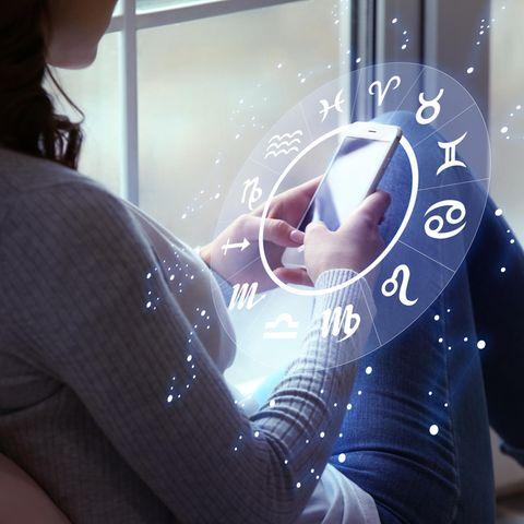Horoskop: Frau blickt am Fenster auf ihr Smartphone