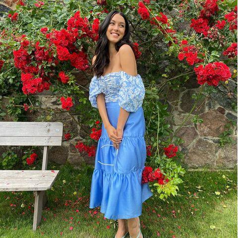 Flowerpower: Rebecca Mir posiert vor einer Blumenwand mit roten Rosen