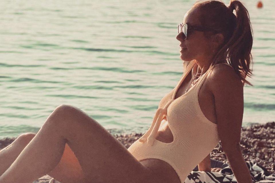 """""""Verhandle mit dem Sommer, ob er nochmal wieder kommt"""", schreibt Annemarie Carpendale unter dieses Foto, das sie im pfirsichfarbenen Badeanzug am Strand zeigt. Ob sie Erfolg hat, wird sich zeigen – umwerfend sieht sie dabei aber allemal aus."""