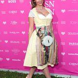 Sila Sahin greift zu einem Dirndl in zartem Gelb und einer bunten Schütze. Als Accessoire dient ihr eine runde Handtasche von Saint Laurent.