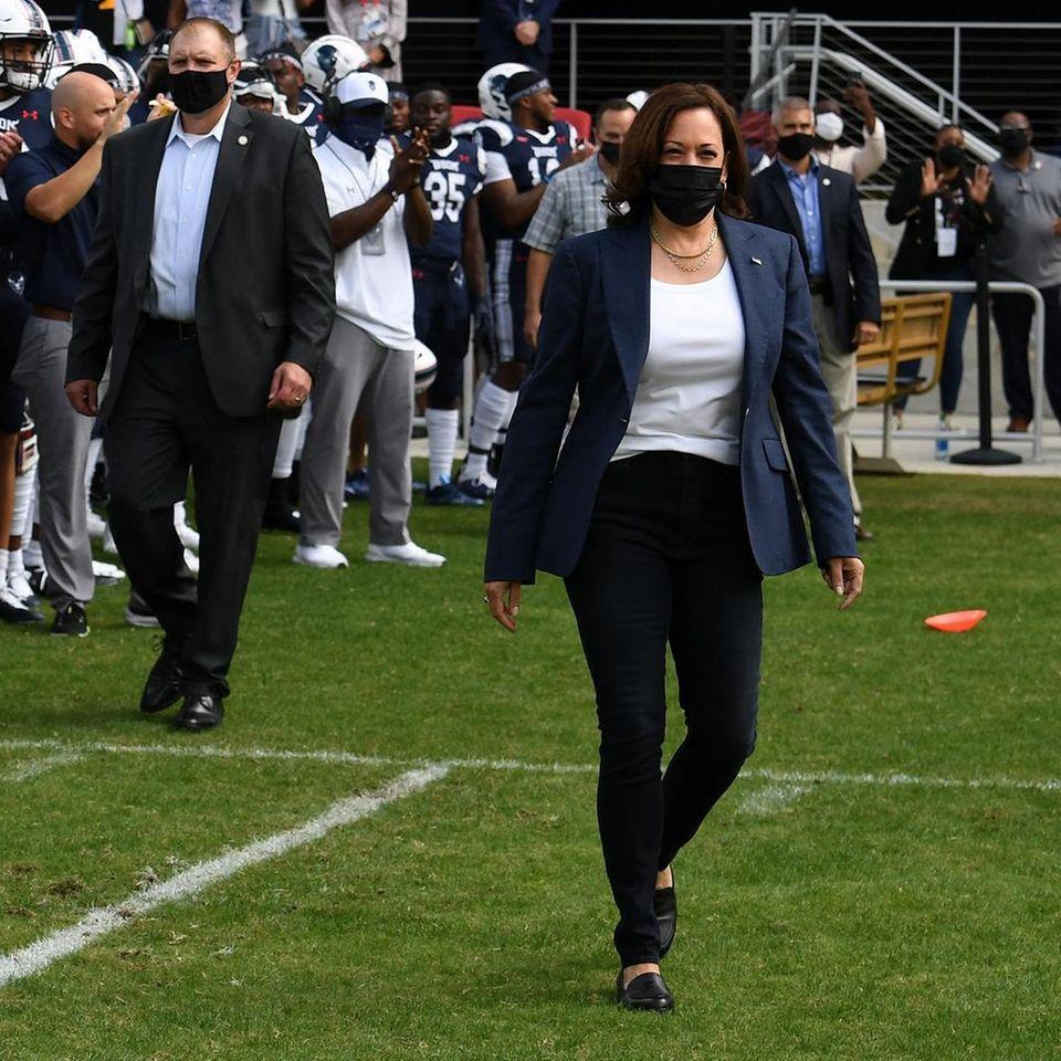 Vizepräsidentin Kamala Harris läuft über ein Footballfeld.