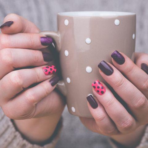 Das verrät Ihre Nagellackfarbe über Sie: Frau mit bunt lackierten Fingernägeln hält Becher.